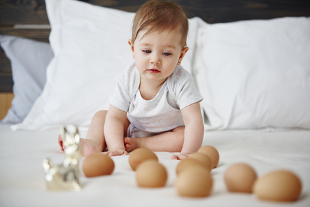 Interested baby girl having fun with eggs