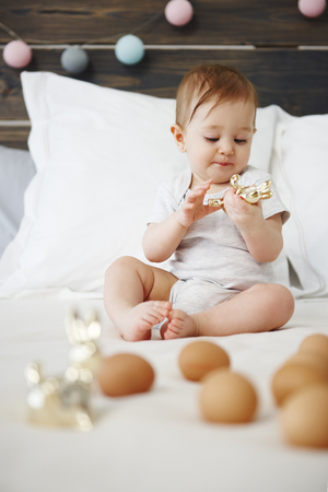 Baby playing with toy on the bed