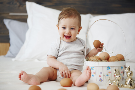 Charming baby girl with easter basket of eggs