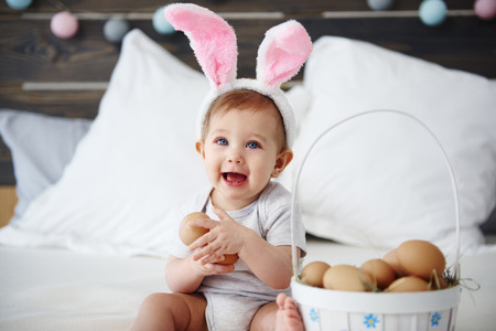 Portrait of baby with bunny ears holding eggs Imagens