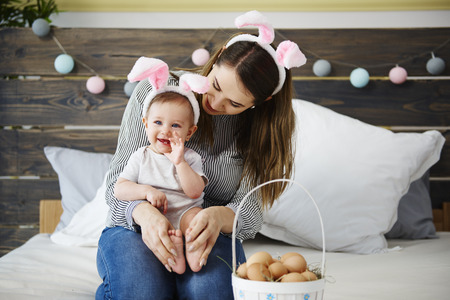 Mum and baby girl celebrating Easter morning in bed