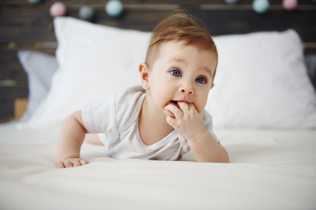Portrait of baby lying on the bed Imagens