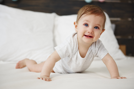 Portrait of baby crawling on the bed Imagens