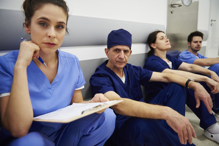 Group of tired surgeons after long day at work  Stockfoto