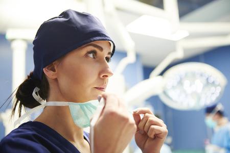 Chirurgo femminile che si prepara per l'operazione Archivio Fotografico