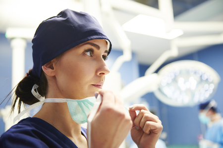 Female surgeon preparing for the operation  Imagens
