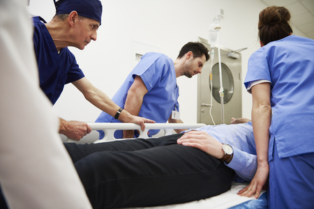 Side view of doctors running to the operating room Stock Photo