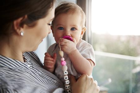 Ujęcie młodej mamy niosącej córeczkę
