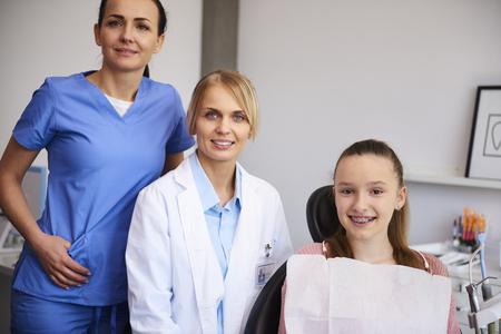 Portrait de deux orthodontistes souriants et enfant dans le cabinet du dentiste