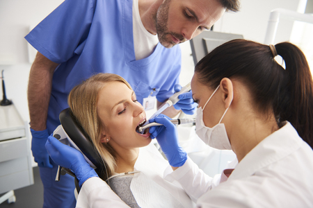Young woman is getting treatment in dentist's office Foto de archivo
