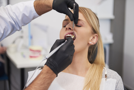 Stomatologist giving woman anesthesia in dentists clinic