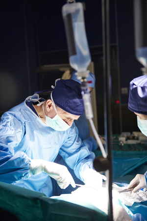 Senior surgeon during serious operation in darkness Stock Photo