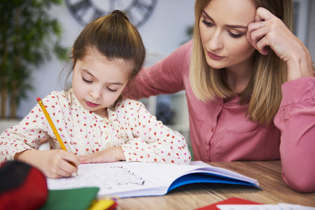 Focused mother helping child with homework