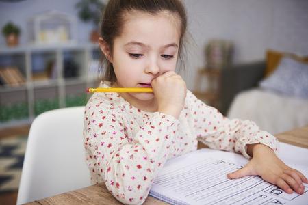 Ragazza concentrata che fa i compiti a casa