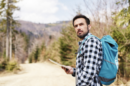 Hiking man with backpack and tablet enjoying at view