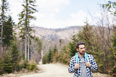 Front view of hiking man with backpack admiring at view Stock Photo