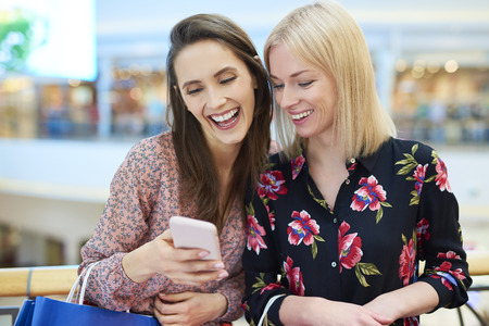 Happy friends using mobile phone during shopping in shopping mall Stock Photo