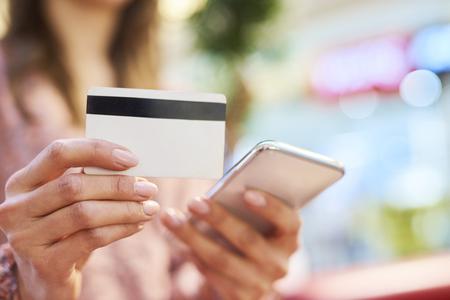 Mujer con teléfono móvil y tarjeta de crédito durante las compras en línea Foto de archivo