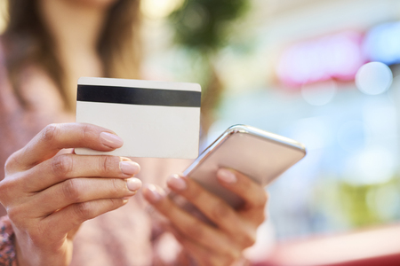 Woman using mobile phone and credit card during online shopping Фото со стока