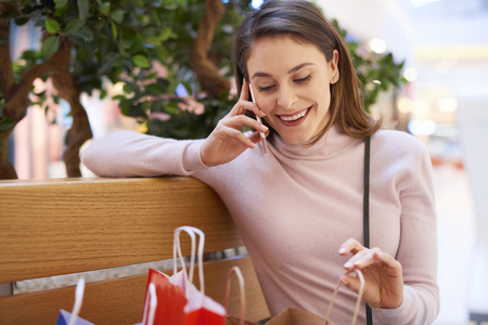 Young woman talking by mobile phone after big shopping