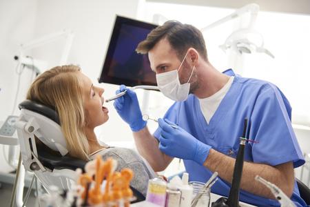 Focused dentist using dental drill and dental mirror