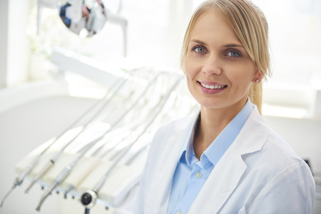 Portrait of smiling dentist in medical uniform in dentists clinic