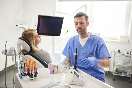 Male dentist doing him work in dentists clinic