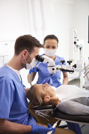 Dentist and his assistant working with dental microscope Imagens