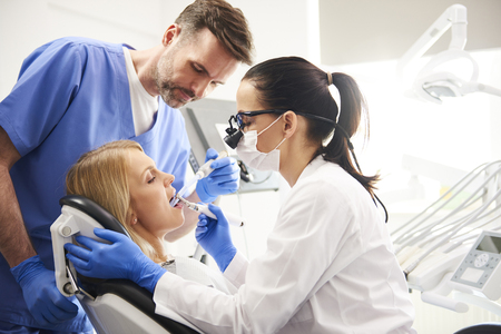 Dentist and her assistant doing their work in dentists clinic Stock Photo