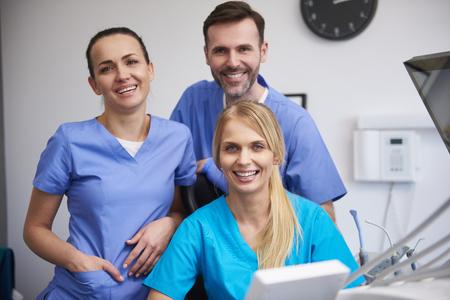 Equipo de estomatólogos felices en la clínica del dentista. Foto de archivo
