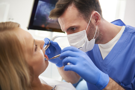 Focused stomatologist treating woman for dental cavity