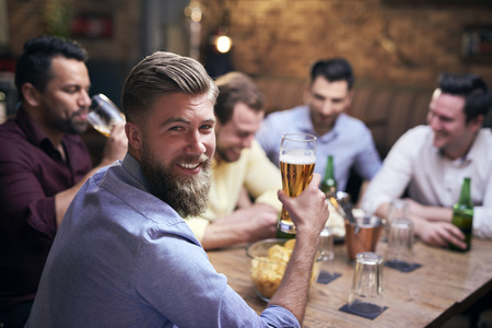 Man drinking beer in pub and friends in the background Imagens