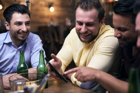 Men using mobile phone during meeting in the pub