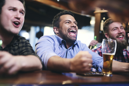 Excited football fans watching american football in the pub Imagens