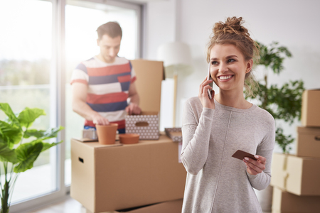Smiling woman talking by mobile phone during moving out Imagens