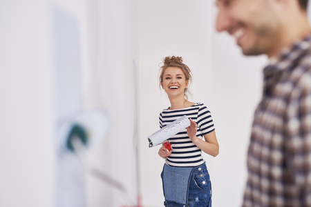 Portrait of smiling woman painting walls in her new flat