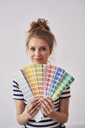 Portrait of smiling woman showing color swatch