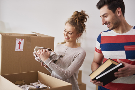 Happy couple packing their stuff into boxes Imagens