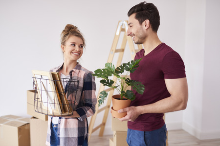 Young couple unpacking boxes of their stuff in new flat