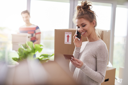 Woman using phone while moving house