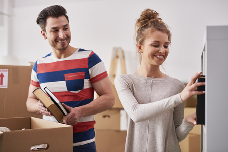 Young couple unpacking moving boxes in new flat Imagens