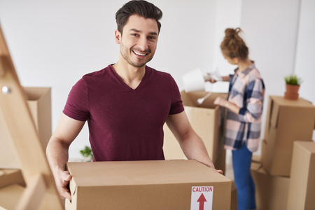 Smiling man moving into new home and unpacking his stuff