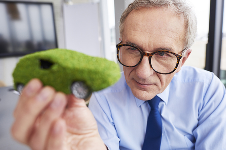 Businessman looking at eco friendly car
