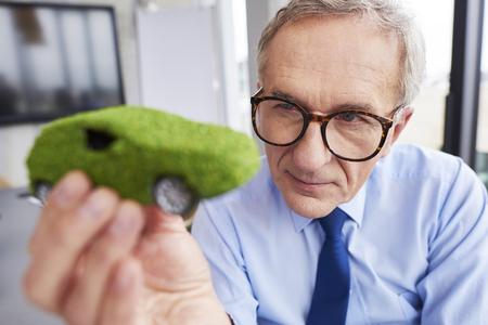 Businessman looking at eco friendly car Foto de archivo - 123697992