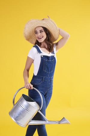 Beautiful woman with watering can in studio shot