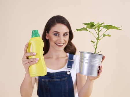 Woman holding bottle of chemical fertilizer and seedling