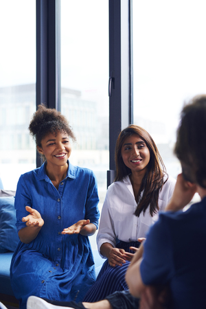 Young adults coworkers exchanging their ideas Stock Photo