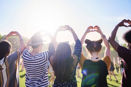 Rear view of friends making a heart with hands