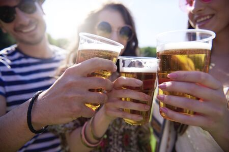 Friends making a cheers outdoors