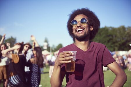 Happy African man drinking beer in festival  Stock Photo